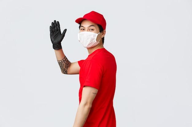 Il simpatico fattorino asiatico torna indietro, dice buona giornata, ciao al cliente soddisfatto, consegna il pacco. corriere in maschera medica e guanti che salutano con la mano, gesto di addio, pubblicità aziendale