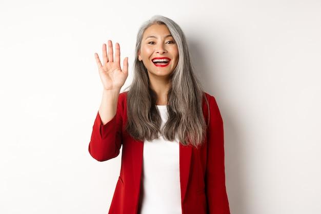 Amichevole asiatica signora senior in elegante blazer dicendo ciao, agitando la mano e salutandovi con un sorriso felice, in piedi su sfondo bianco.