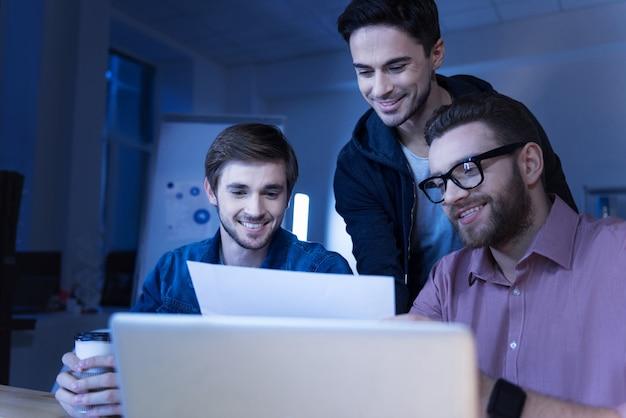 Atmosfera amichevole. programmatori gioiosi piacevoli positivi che esaminano il documento e sorridono mentre si divertono a lavorare insieme