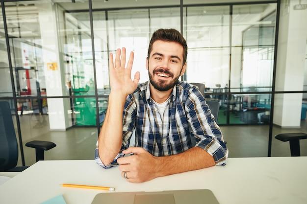 Amichevole ragazzo bruno che agita la mano durante una videochiamata