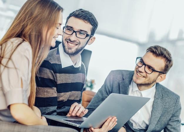Amichevole team aziendale che lavora al laptop e discute di affari