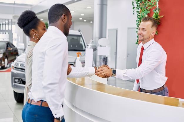 Amministratore uomo caucasico amichevole e consulente della concessionaria accoglie i clienti