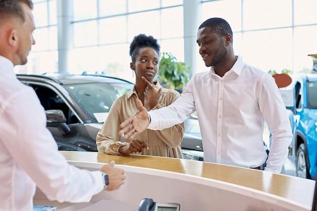 Amichevole manager caucasico saluto i clienti nel salone dell'auto