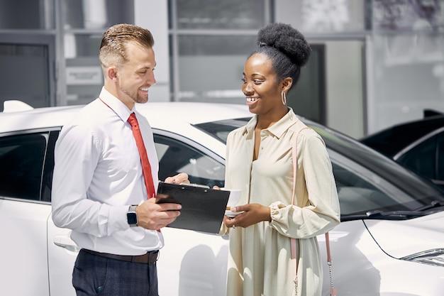 Il venditore caucasico amichevole parla con la donna nera del cliente