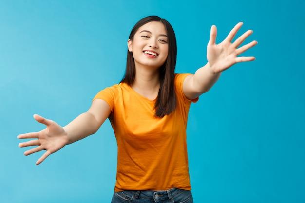 Amichevole ragazza appiccicosa che cammina verso la telecamera con le mani tese per dare un abbraccio stretto, sorridente che abbraccia ampiamente l'amico, felicemente coccole e accogliente fidanzata, sfondo blu in piedi.