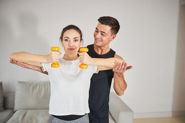 Allenatore amichevole che regola la posizione del braccio di una donna sportiva