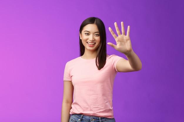 Amichevole ragazza asiatica tenera alza la palma salutando, sorridendo con gioia, addio, accoglie volentieri gli amici che invitano a entrare, salutando, salutando, in piedi sfondo viola