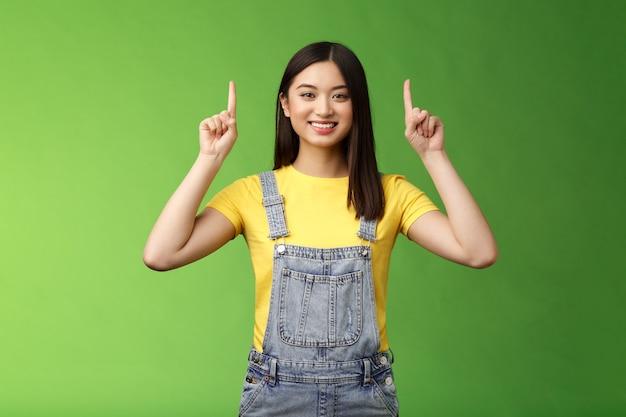 Amichevole carina bella donna bruna asiatica che punta verso l'alto, alza le dita in alto pubblicità, sicura di sé che mostra promo, sorride soddisfatta, introduce un nuovo prodotto, sfondo verde.