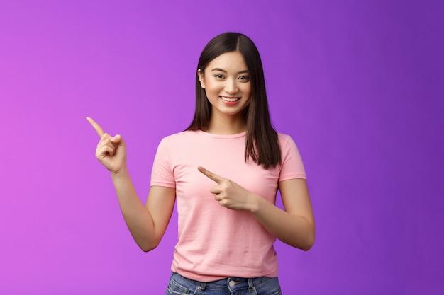 Amichevole simpatica donna asiatica piacevole che mostra la via, indicando promo interessante, indicando a sinistra sorridendo ampiamente, introducendo un prodotto pubblicitario, stando in piedi con uno sfondo viola allegro. copia spazio