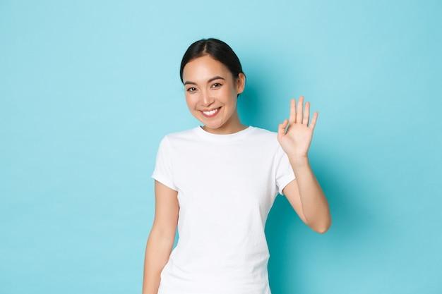 Amichevole ragazza asiatica carina e timida in maglietta casual bianca che dice ciao, sorridente sciocco e agitando la mano in un gesto di saluto, in piedi ottimista su sfondo blu, salutando la persona