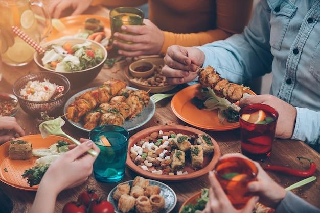 Cena amichevole. vista dall'alto di un gruppo di persone che cenano insieme seduti al tavolo di legno rustico