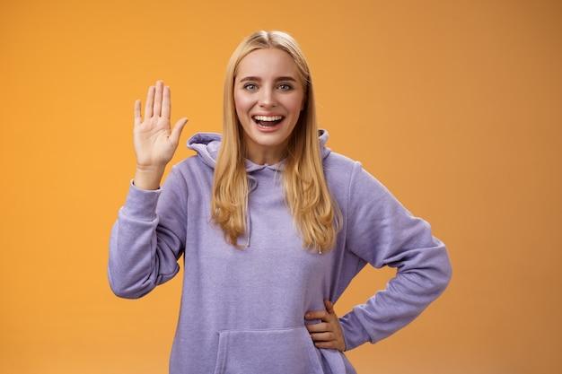 Amichevole eccitato utile affascinante studentessa saluta i nuovi arrivati agitando la palma sollevata ehi ciao gesto saluto accogliente felicemente, in piedi sfondo arancione che sorride ampiamente. copia spazio