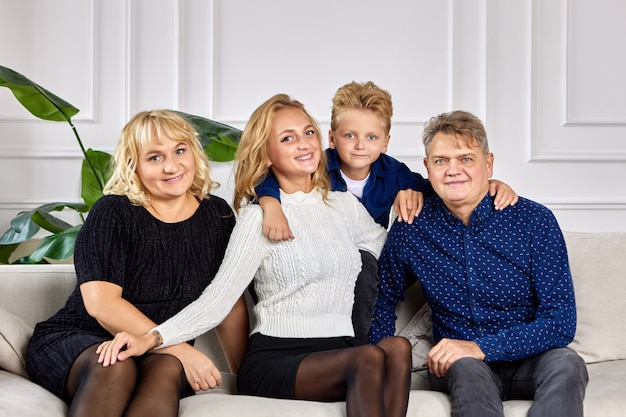 La famiglia europea amichevole è seduta sul divano in soggiorno e sorridente.