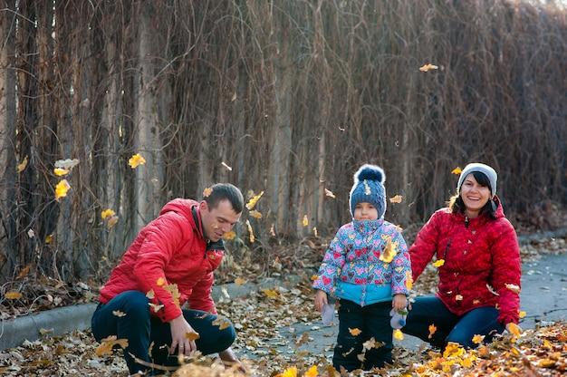 Famiglia amichevole in una passeggiata durante la caduta delle foglie nel parco