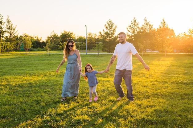 Famiglia amichevole che cammina nel parco e si diverte insieme
