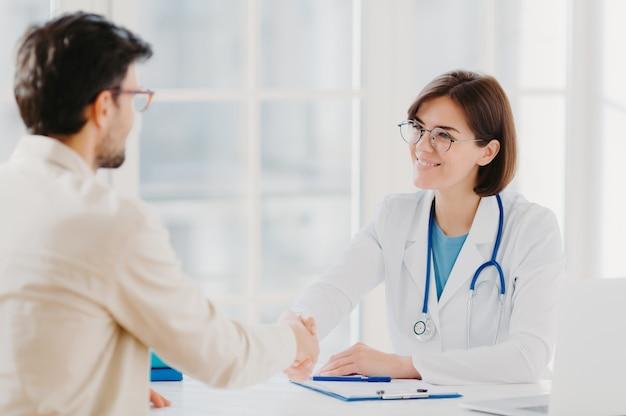 Amichevole dottoressa saluta il paziente con la stretta di mano, posa in clinica privata, si siede uno di fronte all'altro, parla