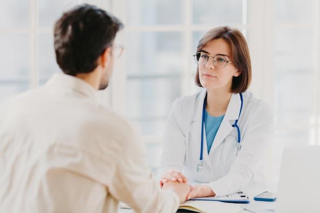 La dottoressa amichevole cerca di sostenere il paziente, gli tiene le mani, dà una consulenza utile e spiega le informazioni mediche, fa l'esame diagnostico, posa nella stanza d'ospedale. sanità, assistenza