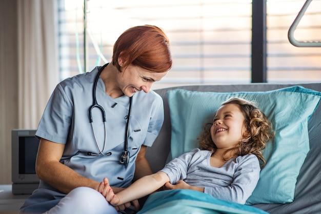 Medico femminile amichevole con lo stetoscopio che esamina piccola ragazza a letto in ospedale.