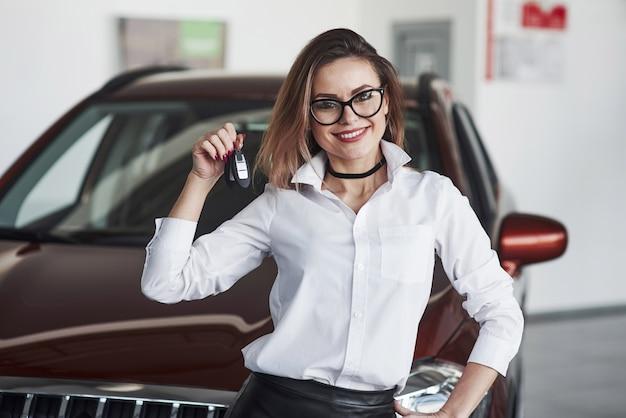 Amichevole manager femminile si leva in piedi contro l'auto rossa nel salone dell'automobile