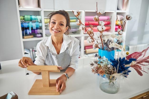 Amichevole fioraio in posa dietro un bancone di un negozio di fiori