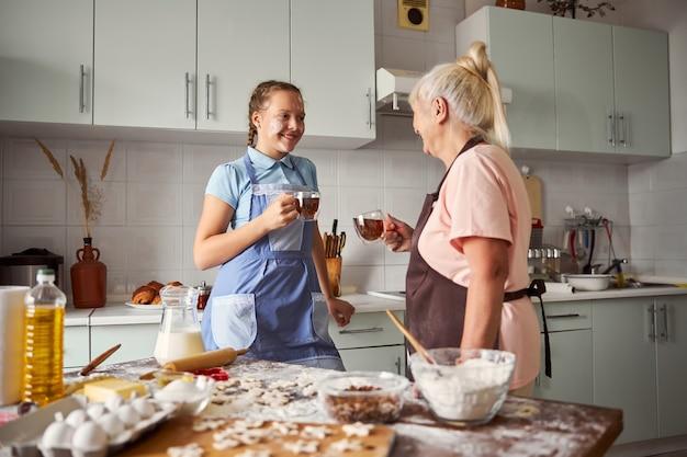 Ragazza amichevole e sua nonna premurosa che bevono tè a casa