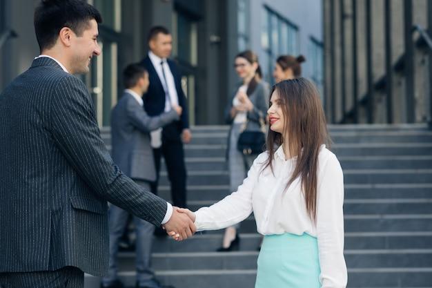Stretta di mano amichevole uomo e donna. incontro di due uomini d'affari all'aperto. persone che si salutano. uomini d'affari che agitano le mani.