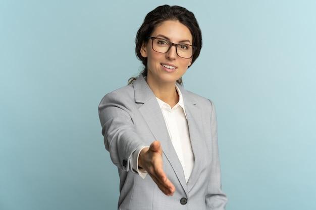 Amichevole ospitale allegra donna d'affari o impiegato indossa giacca sportiva che dà la mano alla stretta di mano