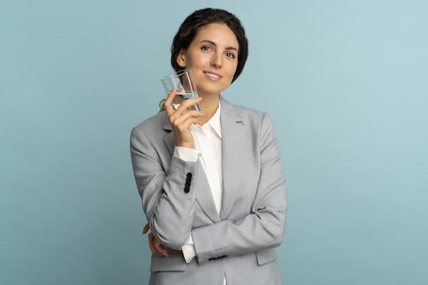 Amichevole agente di assicurazione donna che beve bicchiere di acqua fresca pura, controlla il suo bilancio idrico sul lavoro isolato