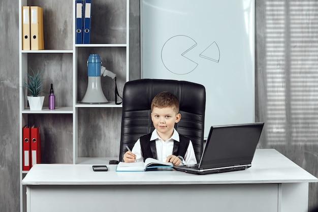 Un ragazzino amichevole che lavora alla scrivania del direttore dell'ufficio