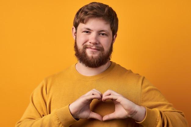 Il ragazzo barbuto dall'aspetto amichevole modella il gesto del cuore, invia amore, beneficenza e volontariato