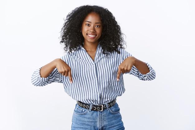 Amichevole e piacevole splendida giovane donna africana dai capelli ricci di 25 anni che indossa una camicetta a righe rivolta verso il basso che sorride felicemente chiedendoti di dare un'occhiata, sbrigati clicca promo, muro bianco