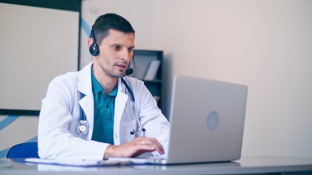 Amichevole maschio medico in camice medico bianco con le cuffie che fanno teleconferenza sul laptop.remote consulenza paziente in linea dall'ospedale sanitario. telemedicina.