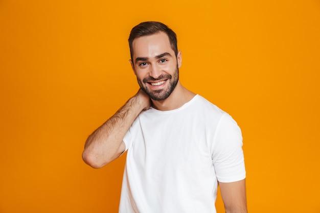 Uomo amichevole con barba e baffi sorridente in piedi, isolato su giallo
