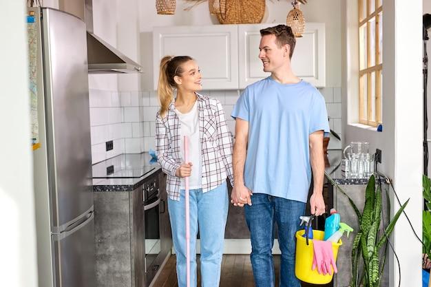 Amichevole coppia sposata felice dopo aver pulito a casa, guardandosi l'un l'altro con amore, sorridendo, soddisfatto della pulizia