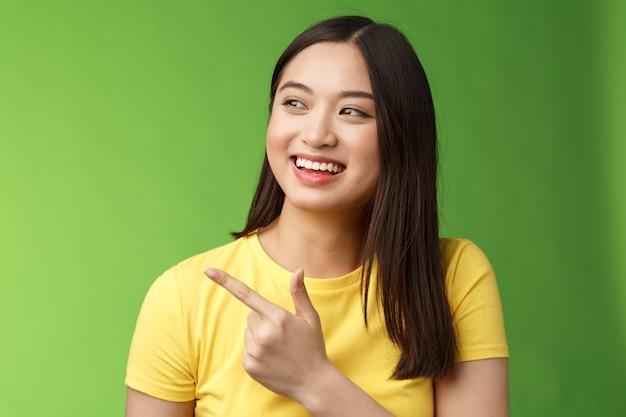 Amichevole ragazza asiatica carina che ha una conversazione divertente, gira gioiosamente verso sinistra, indica un fantastico oggetto fantastico, discuti di eventi interessanti, chatta spensierata, stai in piedi su sfondo verde