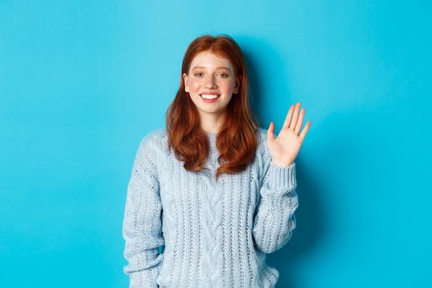 Amichevole ragazza rossa che saluta, agitando la mano in un gesto di saluto e sorridendo, in piedi su sfondo blu