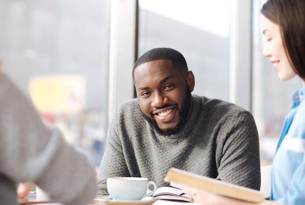 Sorriso amichevole. giovane uomo barbuto bello che sorride e che guarda il suo libro della tenuta dell'amica alla caffetteria.