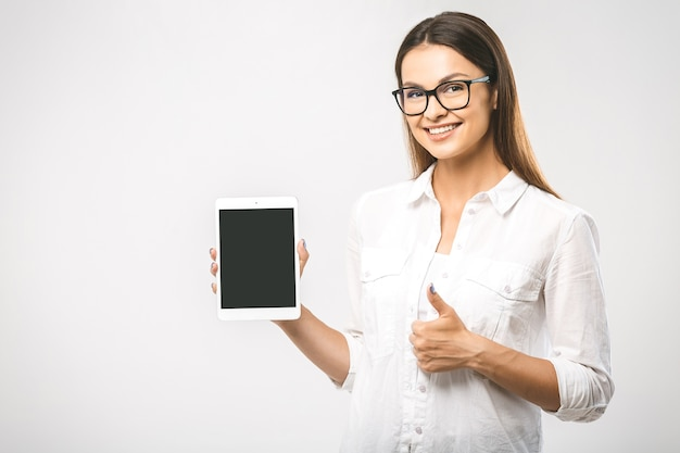 Bella giovane donna sorridente amichevole che presenta un prodotto sul computer tablet