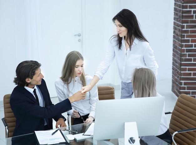 Friendly sorridente imprenditore e imprenditrice handshake sulla scrivania in ufficio