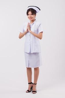 Amichevole infermiera sorridente con gesto di benvenuto in stile tailandese asiatico