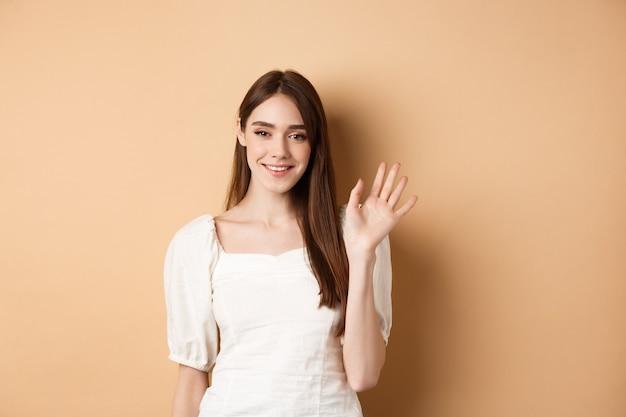 La donna sorridente amichevole saluta, rinunciando alla mano per salutarti, in piedi allegra su sfondo beige.