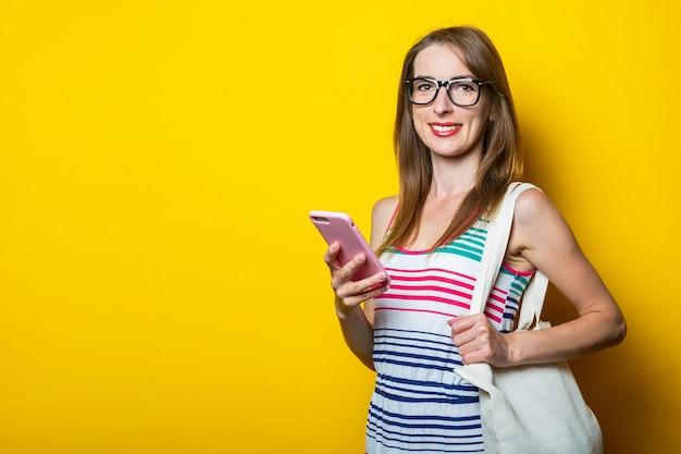Amichevole ragazza sorridente con gli occhiali in possesso di un telefono, con un sacchetto di lino sulla spalla su uno sfondo giallo.