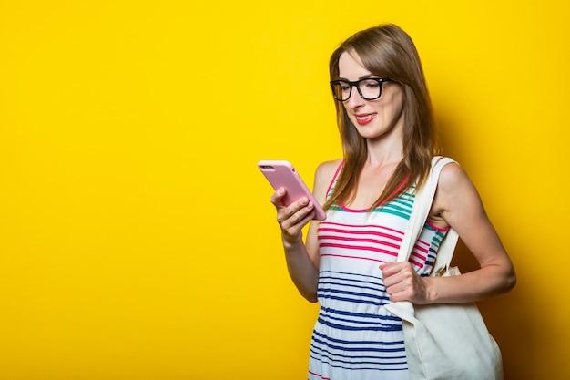 Amichevole ragazza sorridente con gli occhiali guarda il telefono, con un sacchetto di lino sulla spalla su uno sfondo giallo.