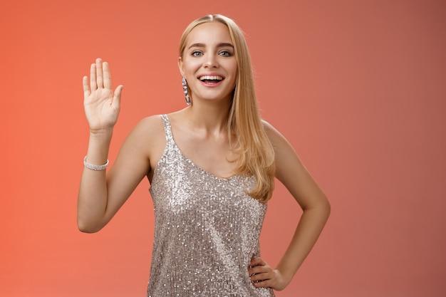 Donna caucasica bionda attraente di fascino elegante amichevole in vita della mano della stretta del vestito scintillante d'argento