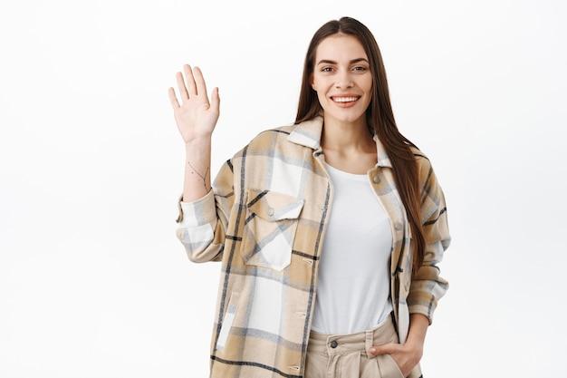 Amichevole donna elegante agitando la mano e salutandoti, salutandoti, dì ehi come va, incontrando persone e dando il benvenuto, in piedi sul muro bianco