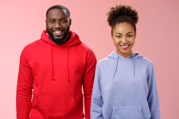 Amichevoli due uomini afroamericani donna in piedi insieme sorridenti ampiamente colleghi presenti progetto collettivo ricevono un buon feedback sogghignando felice come coppia di lavoro, in piedi sfondo rosa