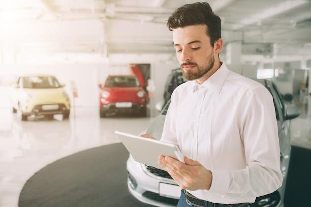 Venditore amichevole del veicolo che presenta le nuove automobili allo showroom.