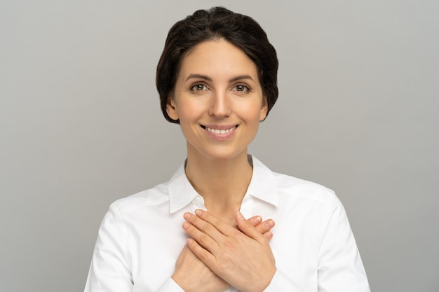 La donna amichevole tiene le mani sul petto, si sente grata per l'amore, l'apprezzamento, la gratitudine e il sostegno