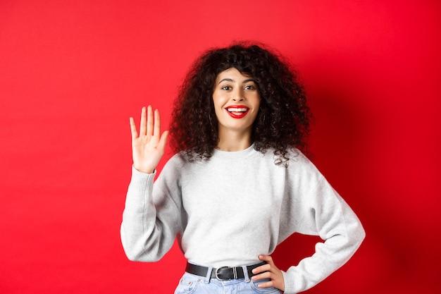 Una donna amichevole con i capelli ricci ti saluta, saluta la mano e saluta, si presenta, in piedi su sfondo rosso.