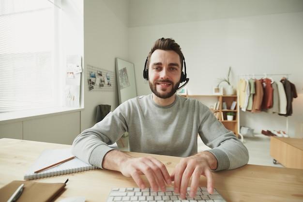 Amichevole giovane barbuto rappresentante dell'assistenza clienti premendo i tasti della tastiera mentre era seduto al tavolo davanti al monitor del computer a casa
